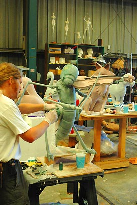 Artist sculpting the Grasshopper in the studio